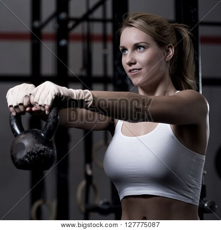 Young and beautiful woman exercising with kettlebell