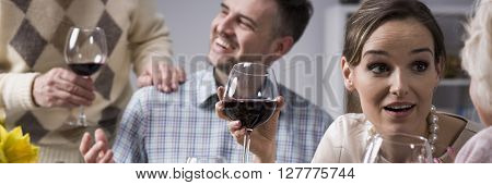 Pretty young woman drinking wine and talking with her mother on family dinner. Behind her husband talking with father-in-law