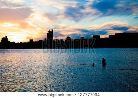 Fisher man fishing with spinning rod in a river at sunset ** Note: Visible grain at 100%, best at smaller sizes