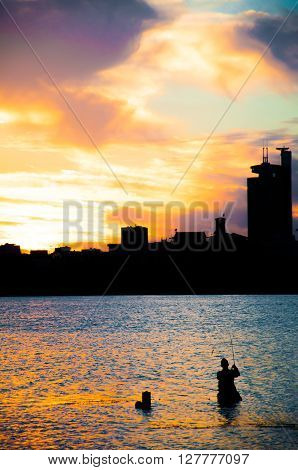 Fisher man fishing with spinning rod in a river at sunset
