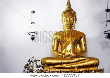 Big Golden Buddha In Lotus Position inside the hall of Wat Pho public temple Bangkok Thailand.