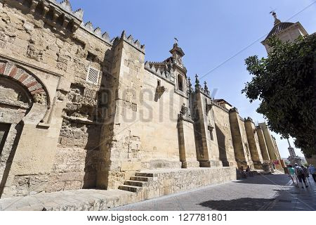CORDOBA, SPAIN - September 10, 2015: Tourists walking along the west facade of the Mosque-Cathedral of Cordoba on September 10, 2015 in Cordoba, Spain