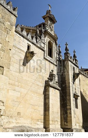 CORDOBA, SPAIN - September 10, 2015: Detail of a small tower with window coat of arms and cross on the west facade of the Mosque-Cathedral of Cordoba on September 10, 2015 in Cordoba, Spain