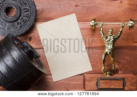 Figure weightlifter and dumbbells on a wooden background