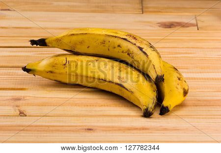 group of yellows plantains on wooden table