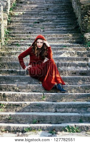 Portrait of beautiful young woman with wavy hair in red dress with hood sitting on old stone stairway