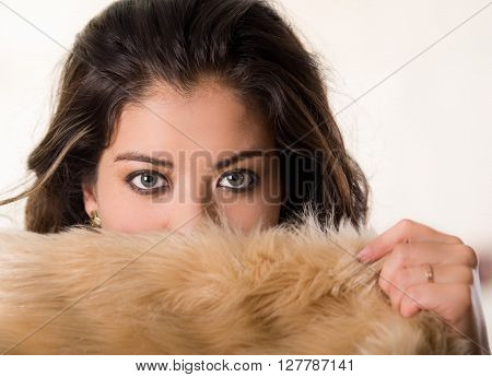 Headshot attractive brunette facing camera covering half her face with brown fur clothing, white studio background.