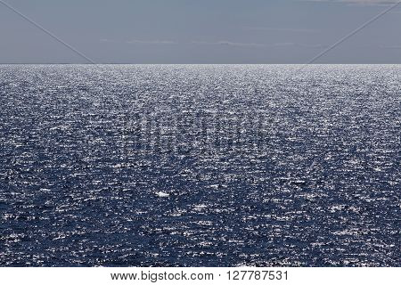 The Sea in back-light. Glittering ocean at sea. Horizon and coastline very far away.