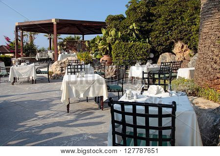 Tables and iron chairs on terrace with flower pots and beautiful garden view, Crete, Greece