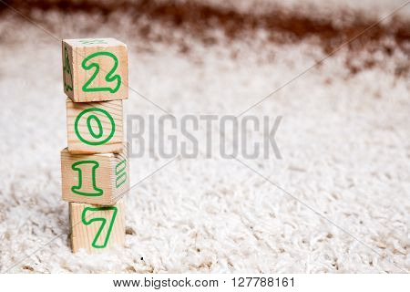 The inscription 2017 made of wooden cubes lying on terry carpet