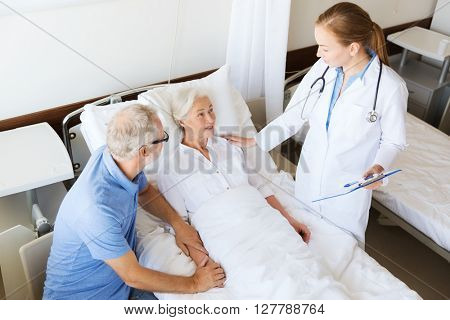 medicine, age, health care and people concept - senior woman, man and doctor with clipboard at hospital ward