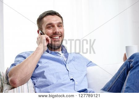 home, technology and internet concept - smiling man with smartphone sitting on couch at home