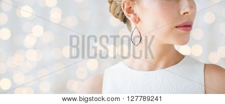 glamour, beauty, jewelry and luxury concept - close up of beautiful woman face with pearl earring over holidays lights background