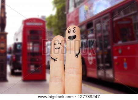 family, couple, travel, tourism and body parts concept - close up of two fingers with smiley faces over london city street background