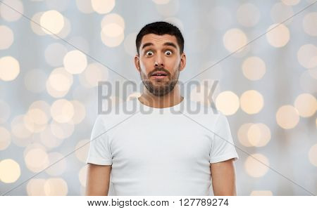 emotion, advertisement and people concept - scared man in white t-shirt over holidays lights background