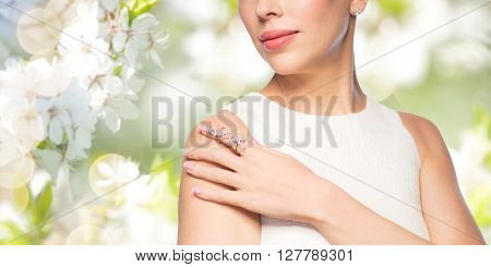 glamour, beauty, jewelry and luxury concept - close up of beautiful woman with golden ring and diamond earring over natural spring cherry blossom