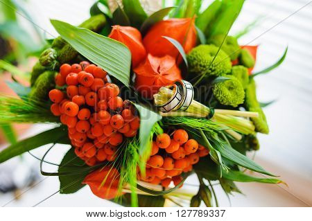 Unusual wedding bouquet with two wedding ring. Bouquet of physalis rowan ear of wheat in a glass vase on the white windowsill.