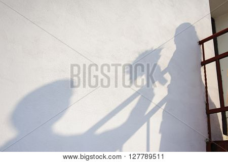 The shadow of the bride and groom on the wall. The shadow of a man giving the bride a bouquet of flowers.