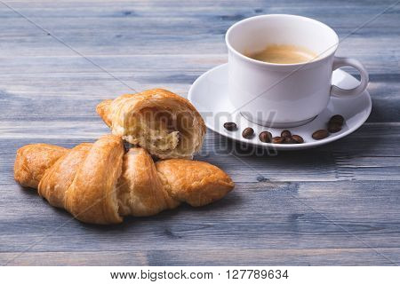 Coffee with freshly baked croissants on the wood background