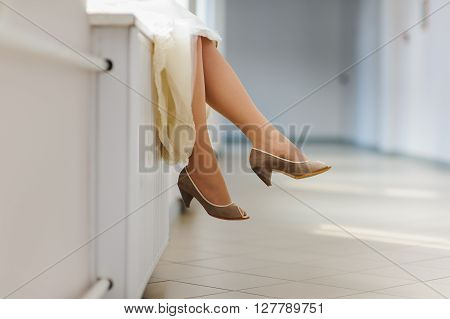 Woman sitting on the windowsill. Legs of woman sitting on a windowsill at the window in a long corridor. ** Note: Visible grain at 100%, best at smaller sizes