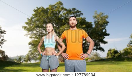 fitness, sport, friendship and healthy lifestyle concept - happy couple exercising over summer park background