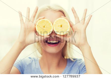 healthy eating, organic food, fruit diet, comic and people concept - happy woman having fun and covering her eyes with lemon slices