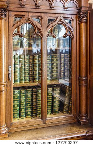 Old wooden bookcase with the books of the nineteenth century