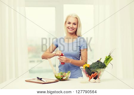 healthy eating, vegetarian food, dieting and people concept - smiling young woman cooking vegetable salad at home