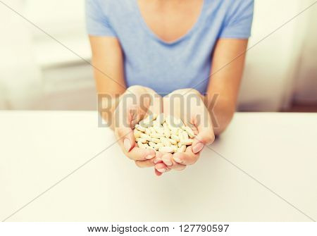 healthy eating, medicine, health care, food supplements and people concept - close up of woman hands with medication or pills at home