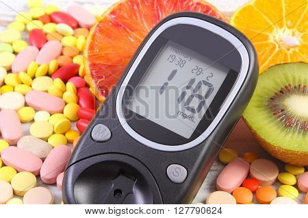 Glucose meter with result of measurement sugar level fresh natural fruits and medical pills tablets and supplements diabetes healthy lifestyle and nutrition