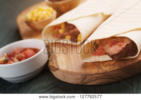 burritos with beef steak, corn, black beans and salsa sauce on wood table, vintage toned