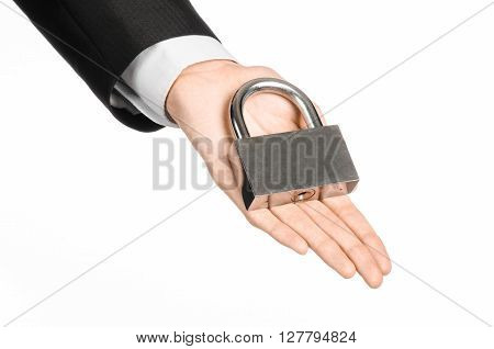 Protection And Business Theme: A Man In A Black Suit Holding A Metal Padlock Isolated On A White Bac