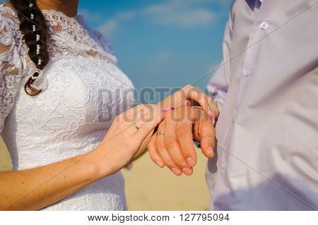 Wedding ceremony on the beach. Man and woman holding hands. Wedding rings. Bride in wedding dress the groom wearing a shirt. Sky and sand in the background.