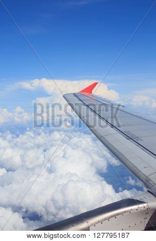 view from aircraft window to see airplane wing and white clouds