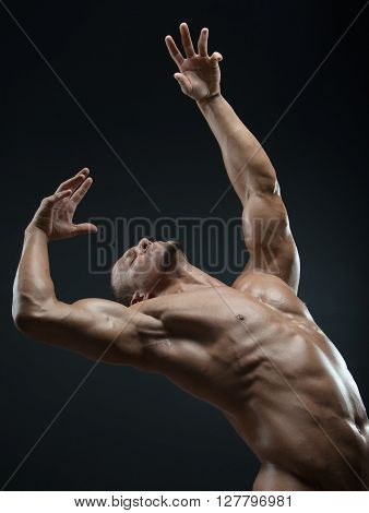 Bodybuilder and strip theme: beautiful with pumped muscles naked man posing in the studio on a dark background shot