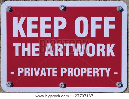 A sign advising to keep off the artwork.