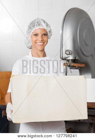 Confident Female Baker Holding Big Bread Loaf