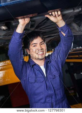 Confident Mechanic Working Underneath Car