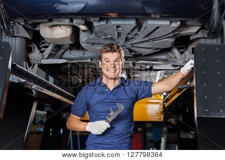 Mechanic Holding Wrench Underneath Lifted Car