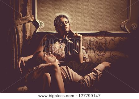Young Flirting Couple Is Laying On The Sofa. Vintage Post Processing.