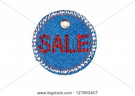 Denim label with the word SALE made rhinestones isolated on a white background