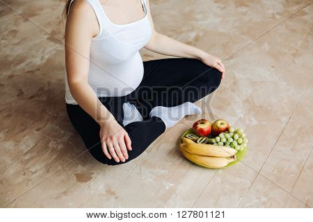 Heathy food for my baby. Pregnant woman holding a plate with fruits.