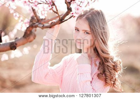 Smiling teen girl 14-16 year old wearing cozy pink sweater outdoors. Looking at camera. Holding peach tree in garden. Teenager hood.