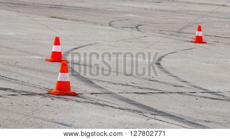 Black traces of protectors on the gray pavement and bright red traffic cones on the racetrack