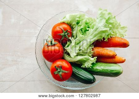 whole fresh vegetables on a plate: lettuce, cucumbers, tomatoes, carrots. lettuce and fresh vegetable close up. Composition with raw vegetables