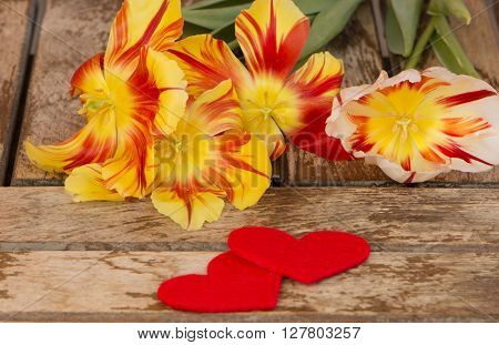 Tulips. Red and yellow tulips on wooden background. Tulips and hearts. Red tulips, Bouquet of tulips for love. Tulips in bouquet, beautiful tulips.