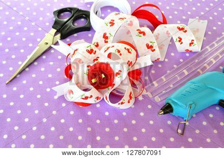 Bright bow of ribbon, children hair accessory, ribbon set, scissors, hot glue gun