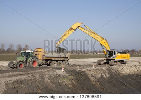 Grootebroek , the netherlands - 17 march , 2016: Cranes at work excavating and creating the ground in a tipper of a tractor