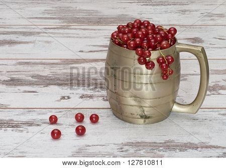 Red currant in an old metal mug on a shabby wooden table. Ripe currant in the old metal mug.