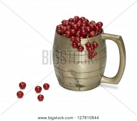 Red currant in an old metal mug. Isolated on the white background. With shadow.